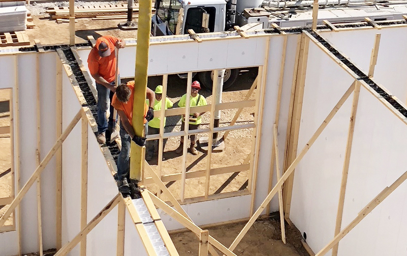 Construction workers pouring concrete walls